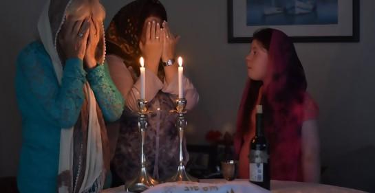 Se ve a dos mujeres mayores con las manos tapándose los ojos  y un pañuelo cubriendo su cabeza, diciendo una bendición junto a un par de velas encendidas. A su derecha, un niña las observa atentamente.