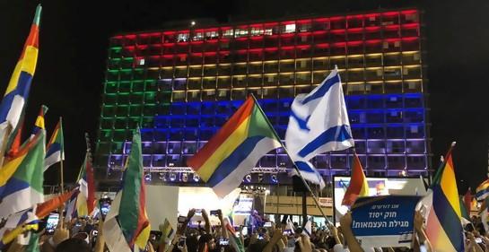 manifestación en Tel Aviv, una multitud presente, se ven cabezas más que nada, manos en alto con banderas de Israel y de la comunidad drusa, Y de fondo, una pared, de la municipalidad de Tel Aviv, encendida con luces que forman la bandera de la comunidad