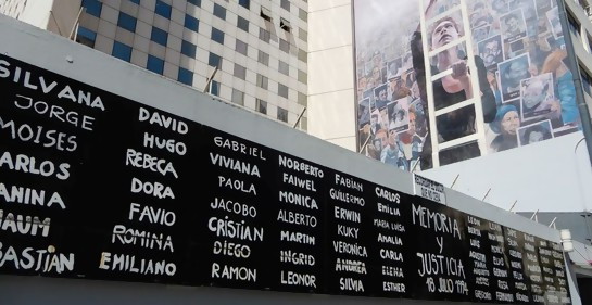 La pared contigua a la entrada a la AMIA en la calle Pasteur tal cual se la ve hoy, con los nombres de los asesinados en el atentado, y la pared pintada del interior.