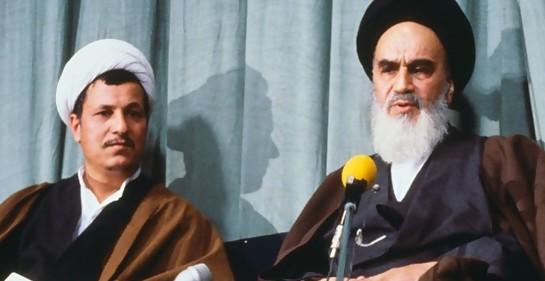 A la izquierda Rafsanjani, que fue presidente de Irán, sentado junto al líder de la revolucion islámica en Irán el Ayatollah Khomeini. Hay dos micrófonos.