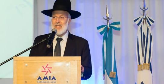 El rabino Davidovich haciendo uso de la palabra en un podio de oradores de AMIA. Vestido de negro, con sombrero negro. De fondo, la bandera de Israel y la de Argenitina.