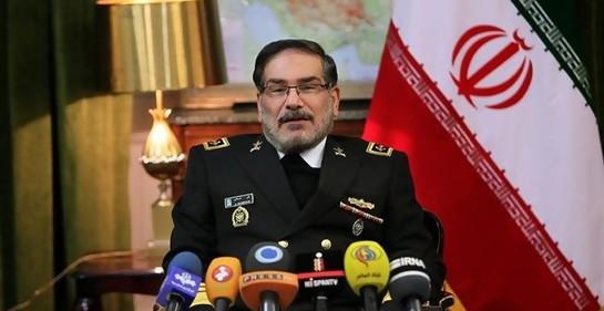 Ali Shmkhani, de uniforme, sentado frente a varios micrófonos. De fondo, a su derecha, la bandera de Irán.