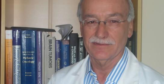El oncólogo infantil Dr Ney Castillo, de túnica blanca, foto medio cuerpo, libros de su biblioteca de fondo