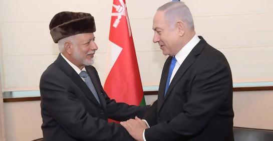 Saludo entre el canciller de Omán, a la izquierda, y el premier isrelí. De fondo, las dos banderas, pero se ve más que nada la de Omán.