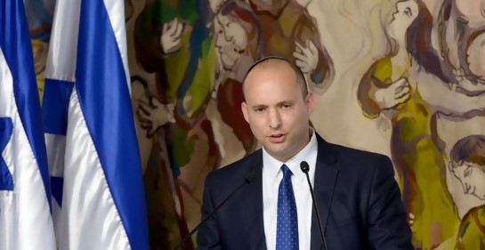 El ministro israelí Naftali Bennett hablando junto a dos banderas de Israel. De fondo, murales de Chagall en el parlamento israelí