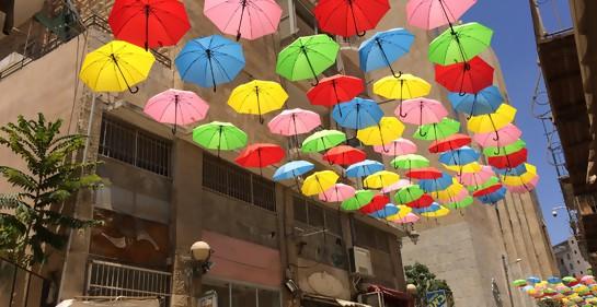 calle peatonal con paragüas abiertos que cuelgan