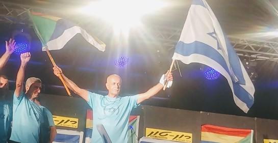 Amal Assad con dos banderas, la de Israel y la de los drusos, una en cada mano, levantándolas en alto.A su izquierda, otro de los participantes en el liderazgo de la protesta drusa. De fondo, en el estado del acto en la plaza Rabin banderas de israel y de