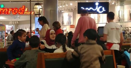 Una mujer con la cabeza cubierta al estilo musulmán, y varios niños, sentados en un café en un centro comercial