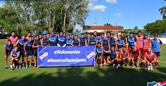 El plantel completo de Nacional en Primera División y el Equipo Técnico, con la pancarta que dice We Remember y Nosotros Recordamos, de fondo azul, con el escudo de Nacional a ambos costados. Letras blancas.