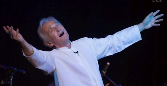 Rafael Goldwasser, de camisa blanca, sonríe, gesticula, con los brazos bien abiertos