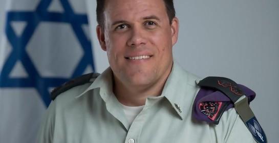 Tte Cnel Jonathan Conricus, de uniforme, boina al hombro, insignias, de fondo la bandera de Israel