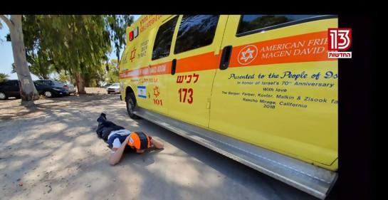 Un paramédico sorprendido por una alarma en el sur de Israel, cumpliendo instrucciones: si no hay refugio cerca, tirarse al suelo y protegerse la cabeza(captura de pantalla canal 11 tv israelí)