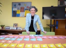 Mariana, sonriente, de pie junto a una mesa llena de piezas de colores