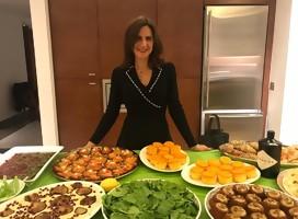 Elli Kriel de pie junto a una mesa con diferentes fuentes multicolores de comida
