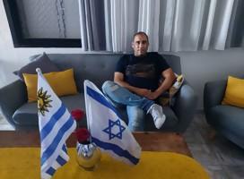 Un hombre sentado en el salón de su casa, de frente dos banderas, de Israel y Uruguay