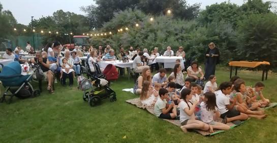 Adultos y jóves en una celebración comunitaria, algunos sentados en sillas y otros en el césped