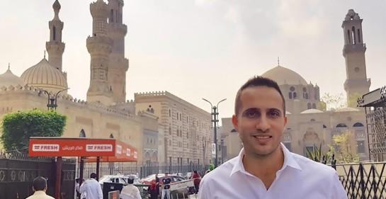 Yonatan Gonen, de camisa blanca, de fondo la calle, transeúnes, hermosos edificios