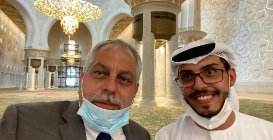 Dos hombres, uno de traje, otro de vestimenta tradicional emiratí, en una mezquita, con barbijos en el mentón