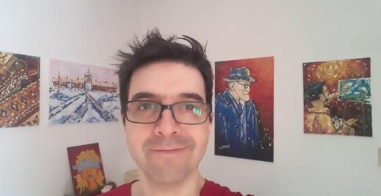 Pablo Solari, de lentes, sonriente, y de fondo sobre una pared blanca, algunos de sus cuadros
