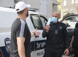 Un policía entregando una máscara a un ciudadano