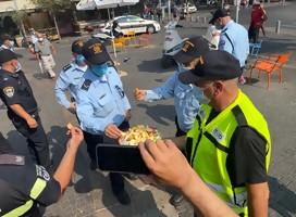 Policías uniformados reciben trozos de manzana con miel