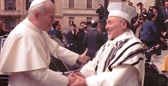 El Papa, de blanco y el rabino, cubierto con el Talit, extendiendo mutuamente los brazos sonriendo ambos y tomándose las manos