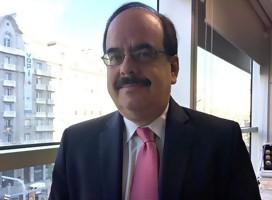 Alberto Fernández, de traje y corbata, sonriente a la cámara, junto a una ventana