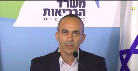 El Profesor Roni Gamzo hablando ante cámaras, entre dos banderas de Israel. De fondo, un banner del MSP de Israel