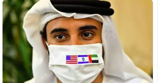 Un emiratí con vestimenta tradicional, con un tapabocas con las banderas de Israel, los Emiratos Arabes Unidos y Estados Unidos