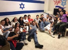 Un grupo de jóvenes sentados en el piso, y detrás, una bandera de Israel