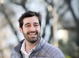 Andrés Burcatovsky, medio cuerpo, sonriente, no mira a la cámara