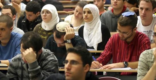 Una clase llena de estudiantes en la universidad, algunos judíos seculares, otros con kipá de judíos religiosos, y en el medio dos jóvenes árabes musulmanascon hijab blanco