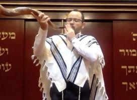 El Rabino Godet, cubierto con el talit, tocando el Shofar