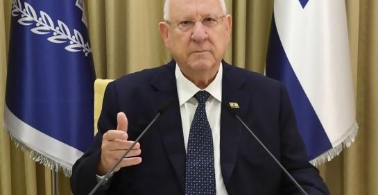 El PResidente Rivlin, sentado, de fondo bandera de Israel y bandera de Beit HaNasí