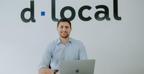 Jacobo Singer junto a su laptop, de fondo el logo de la empresa d.local