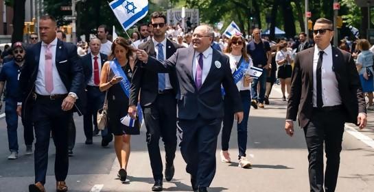 Gente marchando en el medio de la calle, el cónsul de Israel al frente, banderas de Israel, guardaespaldas a los costados