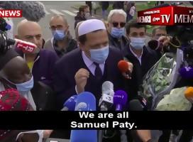 ImamChalgoumi, con tapabocas, hablando a la prensa, rodeado de micrófonos y mucha gente