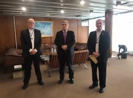 Tres hombres parados en una amplia oficina