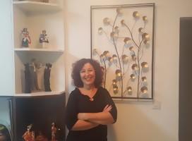 Una mujer vestida de negro, cruzada de brazos, apoyada en la pared junto a un cuadro