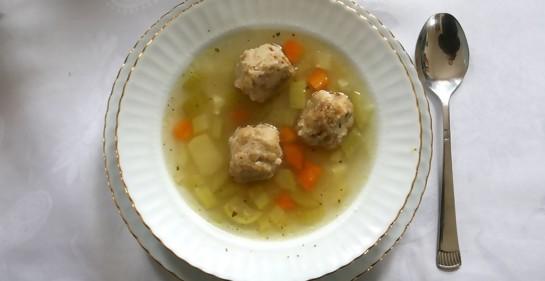 Un plato de sopa, sobre un plato llano. En la sopa, bolas de masa y verduras cortadas. A un costado, una cuchara