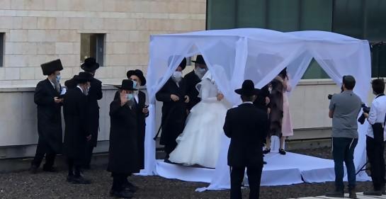 Dentro de la jupá, estructura techada de tela usada en casamientos judíos, una pareja.alrededor varios familiares vestidos de negro con sus prendas tradicionales
