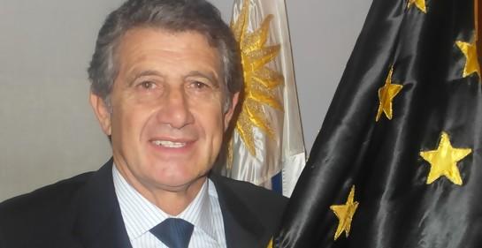 Fernando Morena, de traje, con la bandera de Peñarol. Atrás suyo, el pabellón nacional de Uruguay