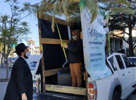 Una camioneta de base de una cabaña , un rabino afuera, una mujer adentro haciendo una bendición con especies