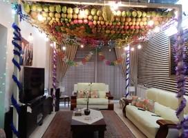 Un comedor, sillones, mesa, paredes adornadas, y bajo el techo, una artesanía de frutas entrelazadas como techo de la cabaña interior