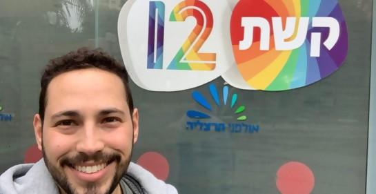 Freddy sonriente, de fondo el logo en hebreo keshet 12, la televisión