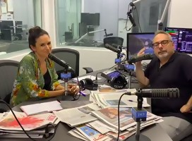 una mujer y un hombre en un estudio radial, micrófono en el medio , mesa llena de diarios