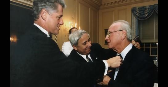 Clinton y Eitan Haber arreglan la corbata de Rabin, sonriente