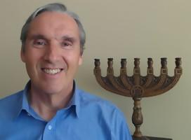 Roberto Cyjon, de camisa azul  . De fondo,una menorá, candelabro judío