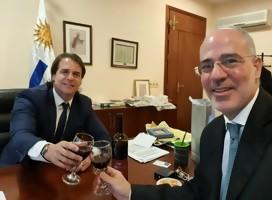 Magen y el Presidente brindando, de fondo la bandera uruguaya