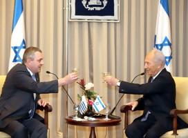 Greiver y Peres brindando. De fondo, la bandera de Israel.